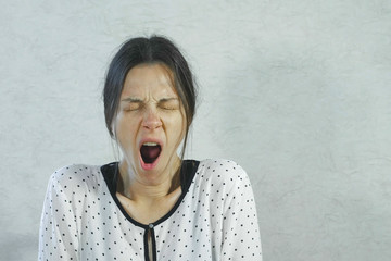 Sleepy tired woman yawns on white background. Wall mural