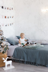 Little beautiful girl playing near a Christmas tree on Christmas eve at home. Little girl relax in a gray  bedroom near the Christmas decoratio