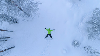 AERIAL: Happy smiling girl making snow angles in fresh snow on snowy mountain