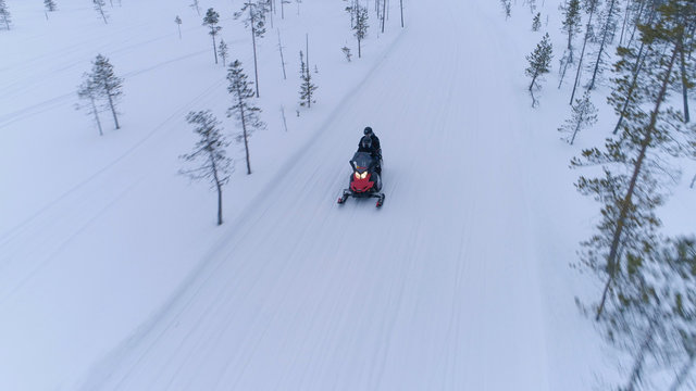 AERIAL, CLOSE UP: Couple riding snowmobile along snowy icy road in wintertime