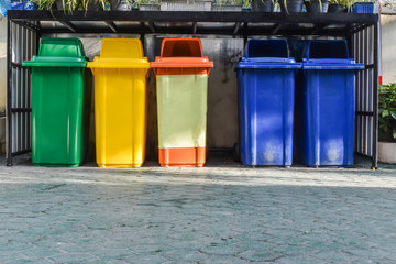 Five colorful recycle bins on the floor.
