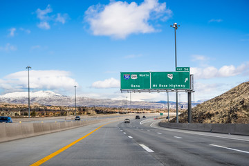 Travelling on the interstate towards Reno; the city's downtown visible in the background; Nevada