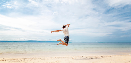 Young man in hat  jumping on the beach in front of ocean with feeling happy and freedom