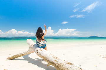 Happy girl on White sand beach and Long-tail boat at Khang Khao Island (Bat island), The beautiful sea Ranong Province, Thailand.