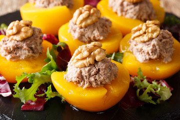 Ripe peaches stuffed with tuna mousse and decorated with walnuts close-up. horizontal