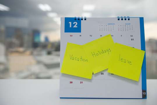 Vacation, holiday and leave on paper note stick on the calendar of December for year end holidays concept