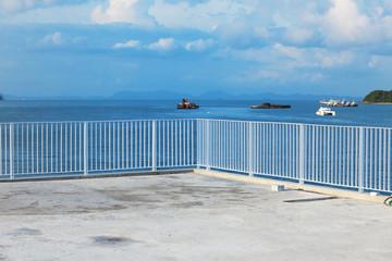 Metal fence on blue ocean background.