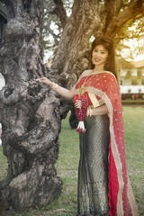 The pretty Thai lady in Middle Thai classical traditional dress suit standing and hold garland is posing in a park.