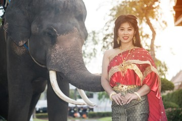 The pretty Thai lady in Middle Thai classical traditional dress suit standing is posing on elephant background.