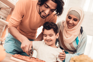 Happy Arabian Family Eating Pizza in Kitchen.