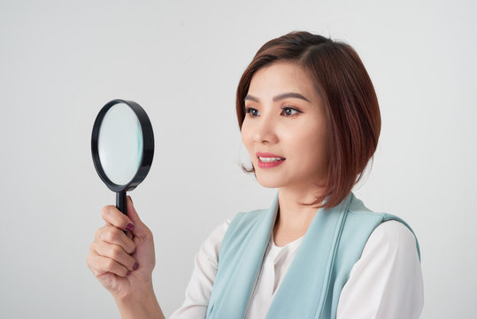 Close-up portrait of cheerful  woman in blue suite looking at camera through magnifying glass, isolated over white background