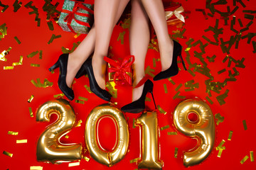 New Year Christmas winter 2019 party celebration concept. Legs of females / women / girls tiny glamour style black shoes on red background with gold balloons  numbers confetti presents gifts top view