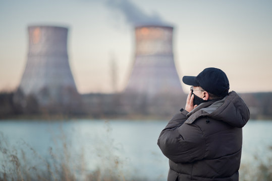 Adult man breathes polluted air by the river