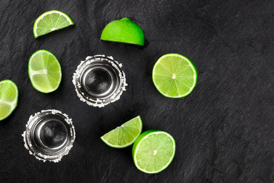 Two tequila shots with lime slices and wedges, shot from the top on a dark background with a place for text