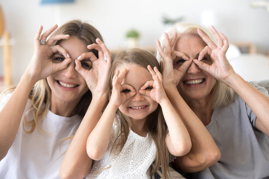 Happy kid granddaughter, mother and grandmother having fun portrait, cheerful 3 generations women family smiling making funny faces looking at camera, grandma, mom and child grimacing together