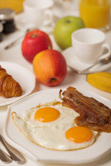 Breakfast time. Fried eggs and bacon. Croissants and orange juice, jam. Coffee with cream or milk. Fruits - bananas, red and green apples.
