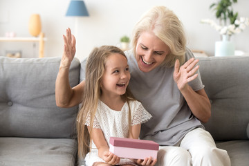 Excited grandchild happy to receive birthday present from loving old grandmother, smiling little kid holding gift box enjoys senior grandma surprise sitting on couch, granny congratulating child girl