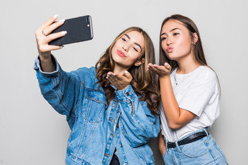 Two mixed race girls friends taking selfie with smartphone, blowing a kiss in the camera, isolated on white background