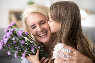 Little preschool granddaughter kissing happy older grandma on cheek giving violet flowers bouquet congratulating smiling senior grandmother with birthday, celebrating mothers day or 8 march concept