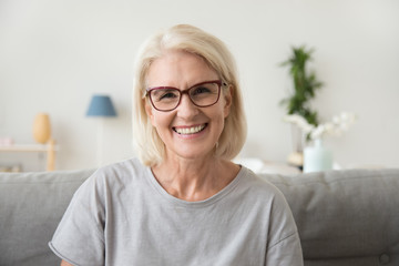 Smiling middle aged mature grey haired woman looking at camera, happy old lady in glasses posing at home indoor, positive single senior retired female sitting on sofa in living room headshot portrait Fototapete