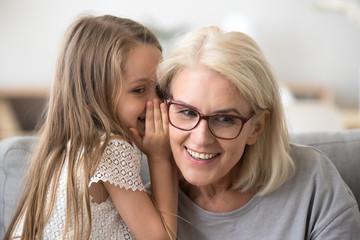 Cute little granddaughter whispering in ear telling secret to understanding smiling grandma, kid girl secretly talking to granny having fun gossiping, trust in grandmother and grandchild relations Wall mural