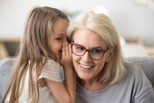 Cute little granddaughter whispering in ear telling secret to understanding smiling grandma, kid girl secretly talking to granny having fun gossiping, trust in grandmother and grandchild relations