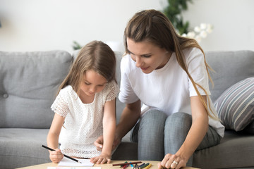 Cute little girl with mom or baby sitter drawing with colored pencils sitting on sofa, nanny or mother teaching preschool kid daughter playing together, educational hobbies for creative child concept