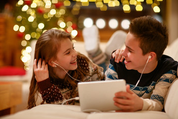 brother and sister with headphones lying and using a tablet and smiling.
