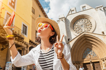 Happy young tourist woman taking selfie at the Tarragona Cathedral, One of most famous places in Catalonia, Spain