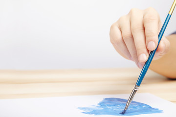 Hand with paint brush. Artist painting a picture.