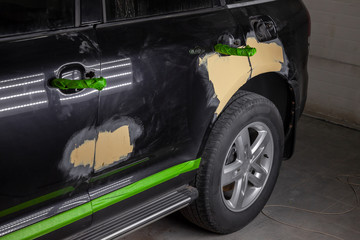 Repair of car body parts in black after an accident and scratches by applying a yellow putty to damaged areas and taped non-damaged elements in a vehicle repair workshop