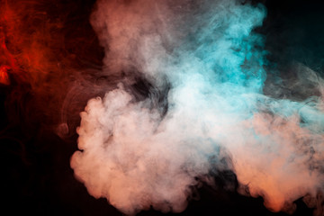 Background of green, white and pink wavy smoke on a black isolated ground. Abstract pattern of steam from vape.