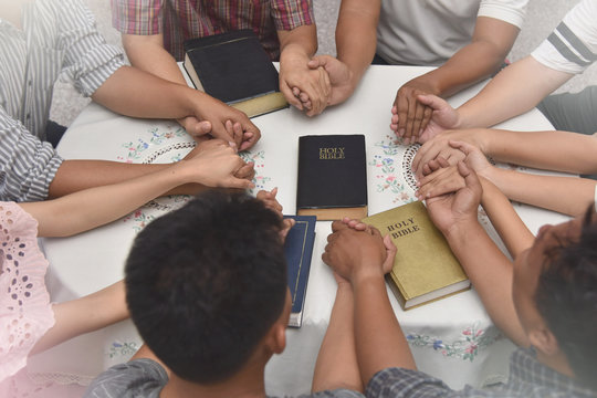 group of people praying hands together. christian praying hand with holy bible.