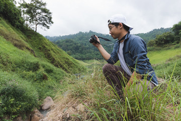 Young Asian traveler man taking photo outdoors scenic nature background. Lifestyle and relaxation concept.