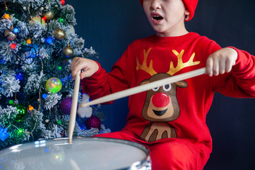 Happy Caucasian childish drummer in carnival costume Santa Claus Deer plays on a new drum set with drum sticks in his hands. Parents bought child drum as gift for Christmas. Lights on Christmas tree