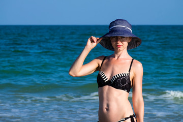 Young beautiful girl in a bathing suit and a striped hat is standing against the blue sea with her hand on the brim hat
