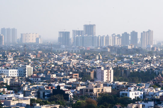 Aerial shot of cityscape with houses, offices and skyscrapers in the distance. Shows the crowded and messy nature of metro cities like Noida, Delhi, gurgaon, lucknow, jaipur, banaglore. Shows the fog