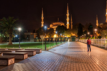 Lone man looking at the Blue Mosque in Istanbul, Turkey at night