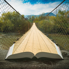 Way by the suspension bridge on the pages of book