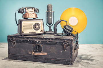 Retro radio from 60s, old copper telephone, studio microphone from 50s, and gold colored vinyl disk...