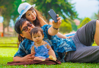 young happy loving Asian Japanese family with parents and sweet baby daughter at city park together with father taking selfie pic with mobile phone