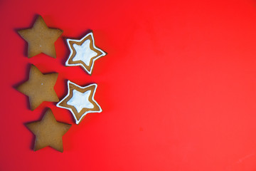 A row of three star cookies. Cookies tied a red ribbon. This fine handcrafted and painted by hand. Cookies in the shape of the star on red background.