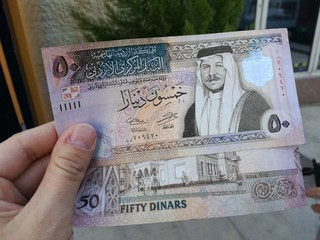 Male hand holding Jordanian dinars banknotes in front of a window.