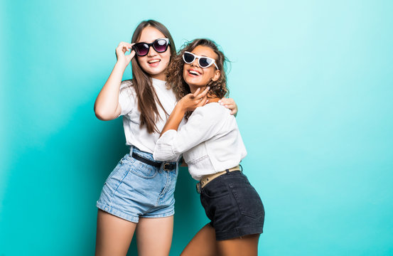Friends forever. Two mixed race cute lovely girl friends in sunglasses posing with smile on blue background
