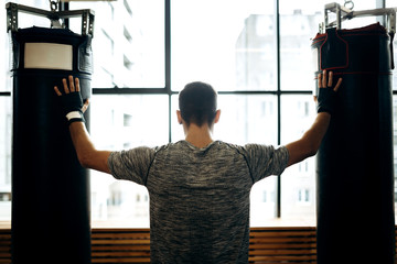 Dark-haired guy stands between two punching bags against the background of panoramic windows in the boxing gym