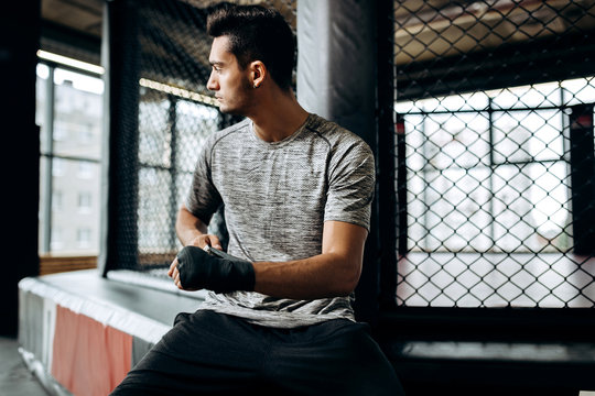 Dark-haired guy dressed in the grey t-shirt wraps a hand bandage on his hand in the boxing gym