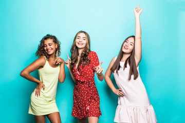 Joyful tanned three european girls posing with pleasure during rest with friends. Funny african young woman dancing in studio enjoying free time with university friends. Wall mural