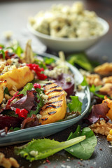 Grilled quince salad with baked and fresh grated beetroot, blue cheese, walnuts on rustic table