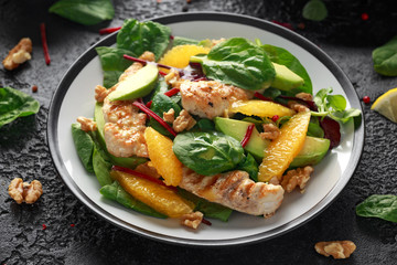 Grilled chicken with orange and avocado salad on rustic background