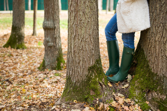Closeup of legs of a woman in green rubber boots standing between two large trees. After the rain, in the open air